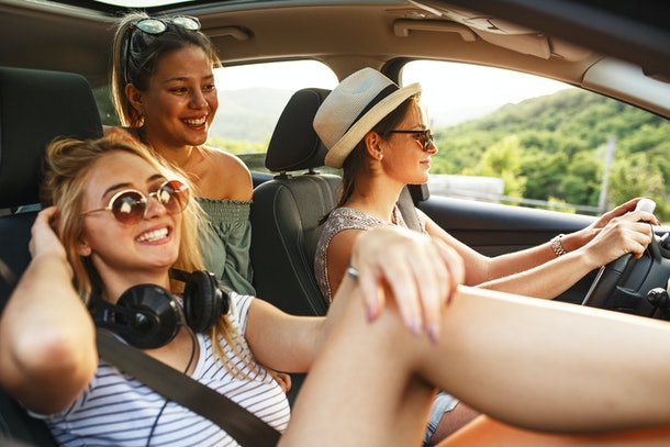 Three friends smile in a car on a sunny day while taking a road trip.