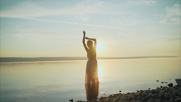 silhouette of a dancing girl on a background sunset. beautiful girl dancing and having fun outdoors. Girl dancing at dawn
