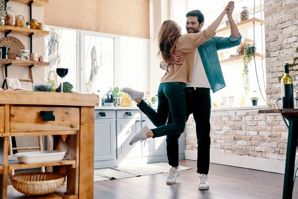 A couple dressed in casual outfits and sneakers laugh and embrace in the kitchen on a sunny day.