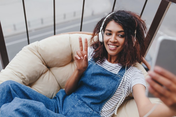 A woman in overalls smiles on a chair for a selfie.