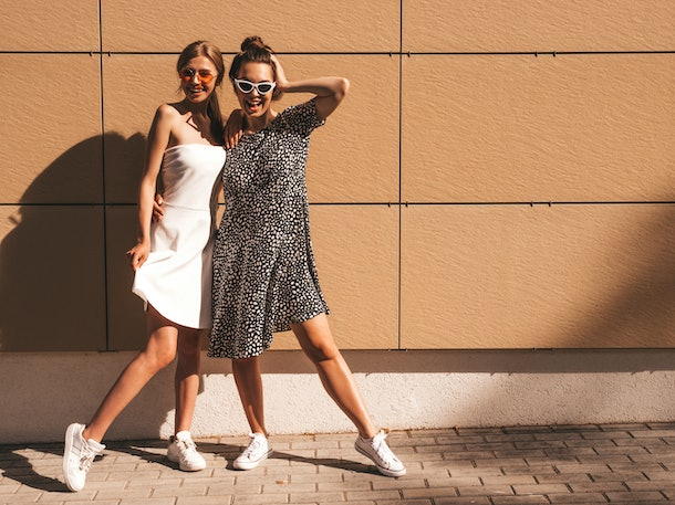 Two trendy girls in sunglasses, white sneakers, and sundresses pose in front of a tan wall on a sunny day.