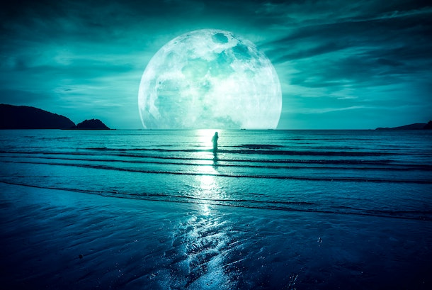 Super moon. Colorful sky with bright full moon over seascape and silhouette of woman standing in the sea . Serenity nature background, outdoor at gloaming. The moon taken with my own camera.