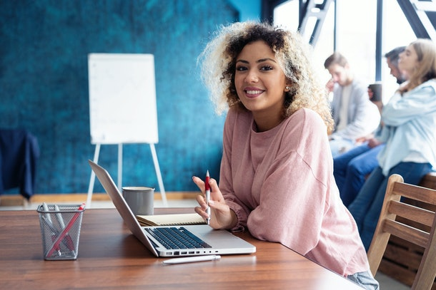 Beautiful business African lady is looking at camera and smiling while working in office. Attractive female manager sitting at desk