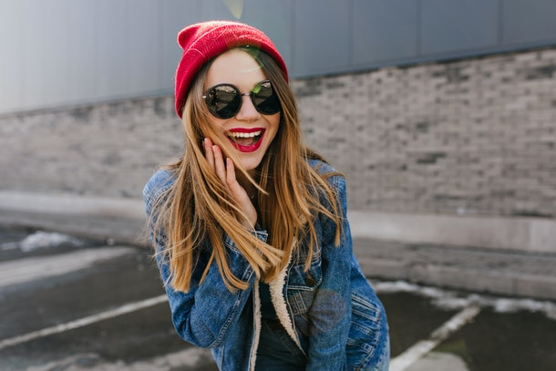 Lovable european girl in trendy black glasses laughing in spring weekend. Outdoor photo of dreamy female model in casual outfit smiling on urban background.