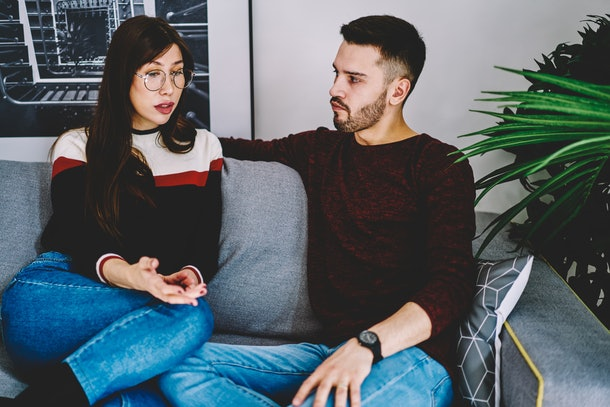 Serious husband and wife concentrated on solving problems of their marriage during leisure time on comfortable sofa in living room, girlfriend and boyfriend have discussion during dispute at home