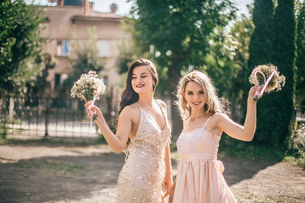 Two bridesmaids dressed in pink dresses hold up their bouquets at a wedding they're attending.