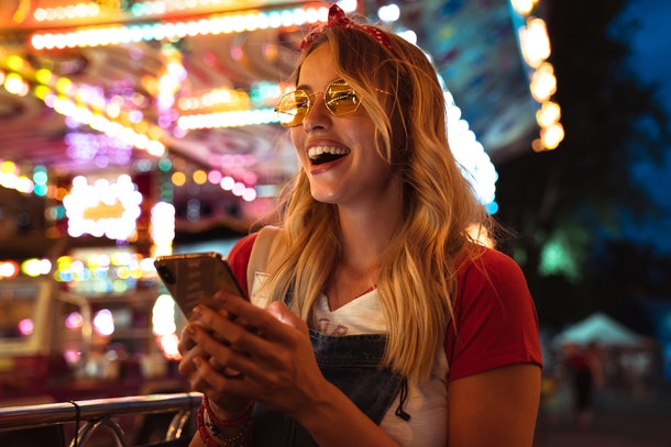 A blonde woman wearing sunglasses and a red headband laughs while holding her phone at a carnival at night.