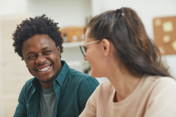 Happy multiethnic young couple talking to each other and spending funny time together