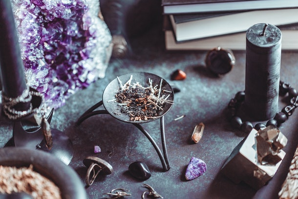 Smoked herbs on a witch's altar for a magical ritual among crystals and black candles.