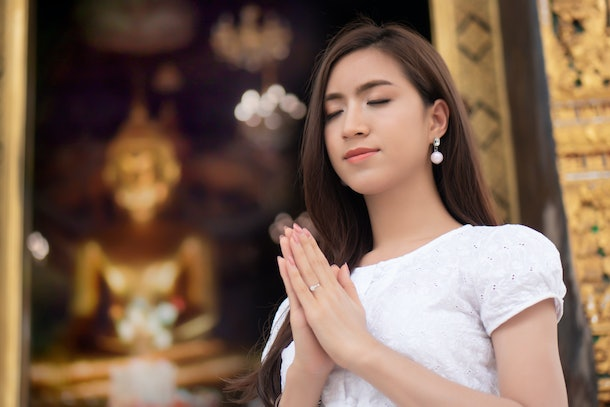 Religious Asian buddhist woman praying. Female buddhist disciple meditating, chanting mantra with prayer hand to the statue of lord Buddha in temple hall; concept of asian faith, belief, spirituality