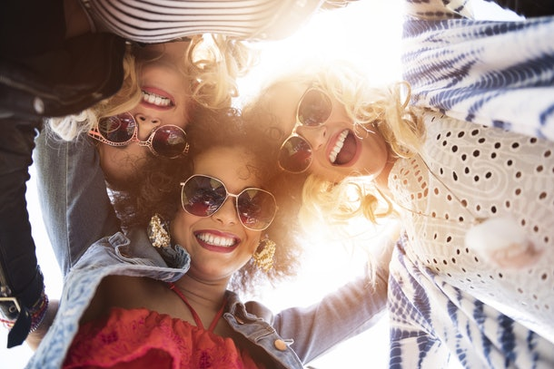 Three friends dressed in spring attire and sunglasses laugh, huddle, and look down.