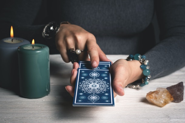Tarot cards in fortune teller hands concept.