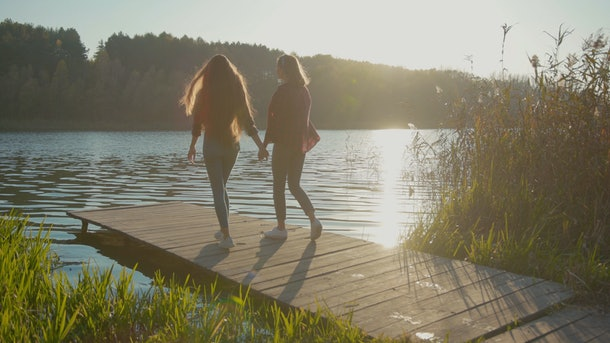 NEW YORK - April 5, 2019: Young attractive women couple walking together on bridge at beautiful lake holding hands enjoying summer weather sunset in gorgeous landscape. Love, relationship concept.