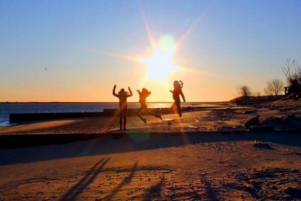 Three friends jump in the air on the beach at sunset.