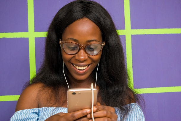 A happy woman standing in front of a bright purple wall looks down at her phone.