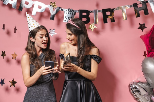 Two friends dressed up for a birthday celebration hold champagne flutes and their phones.
