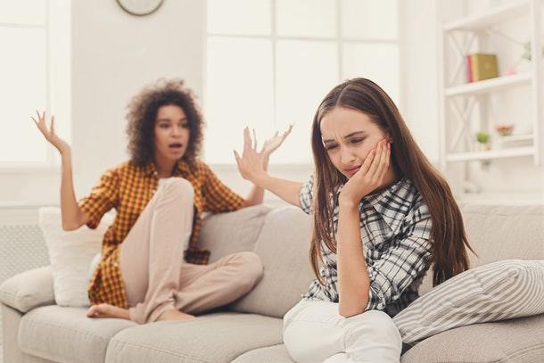 Two female friends sitting on sofa and arguing with each other. Friendship, quarrel, female disagreement, copy space