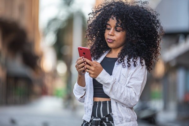Young curly hair black woman walking using cell phone. Texting on street. Big city.