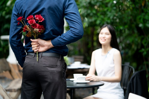 A man is proposing marriage to a smiling woman with a lovely flower bouquet in a beautiful garden, lover and couple concept, surprising proposal