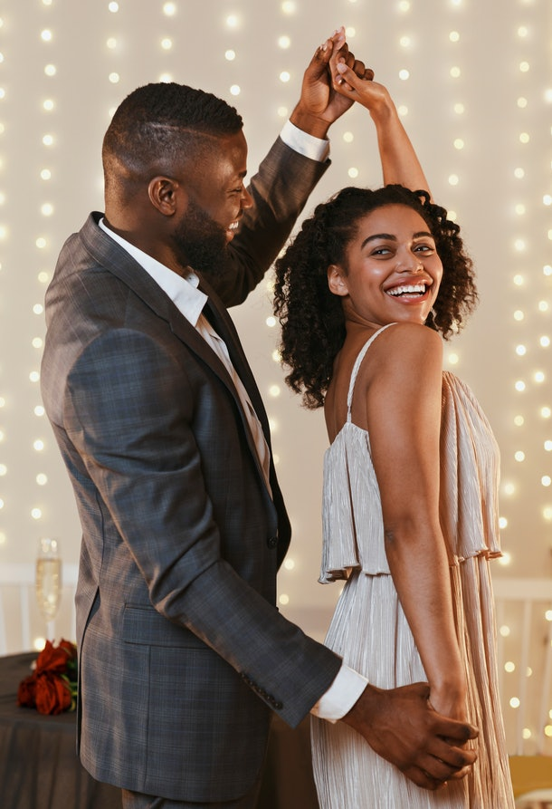 A young couple in fancy attire dances in a restaurant with fairy lights strung up.