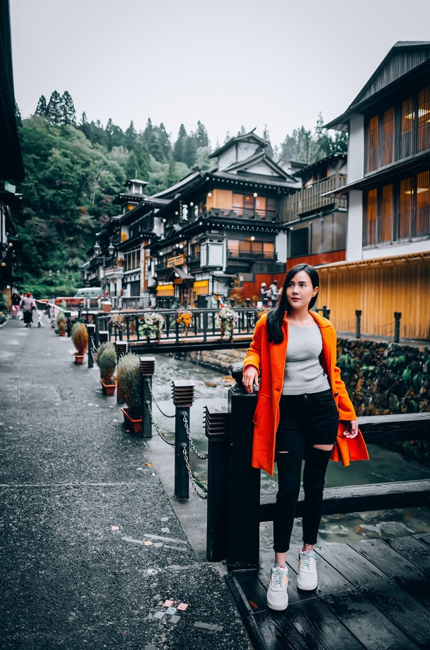 A young woman poses for a photography in a bright red jacket while traveling in Japan.