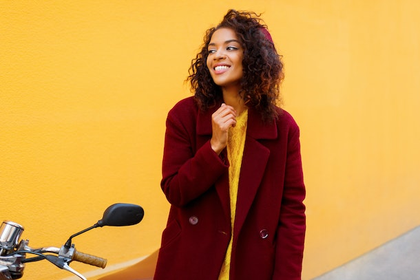 Fashionable black girl in  winter outfit and accessories posing on yellow background. Wavy hairs. Fluffy sweater