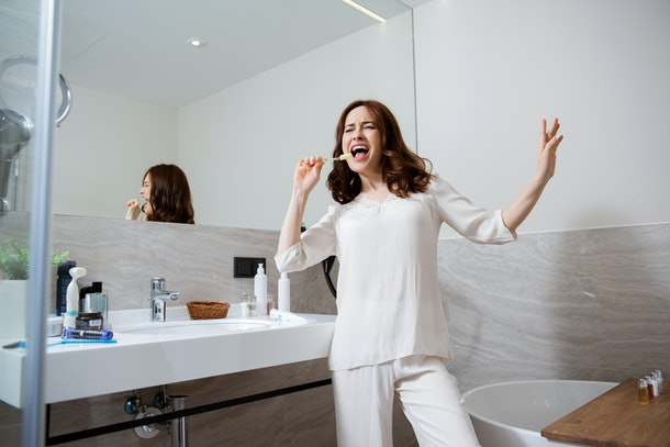 Playful young lady looking expressive and joyful while singing and gesturing in the bathroom with a toothbrush instead of a microphone