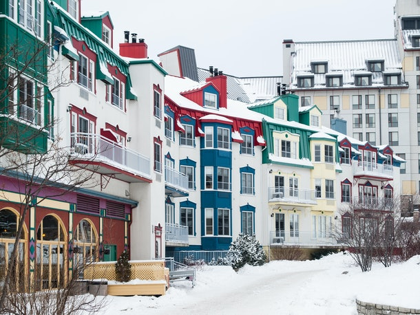 Snow covers colorful buildings in Mont Tremblant, Canada.