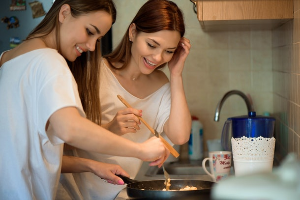 Two women smile and cook a meal in the kitchen.