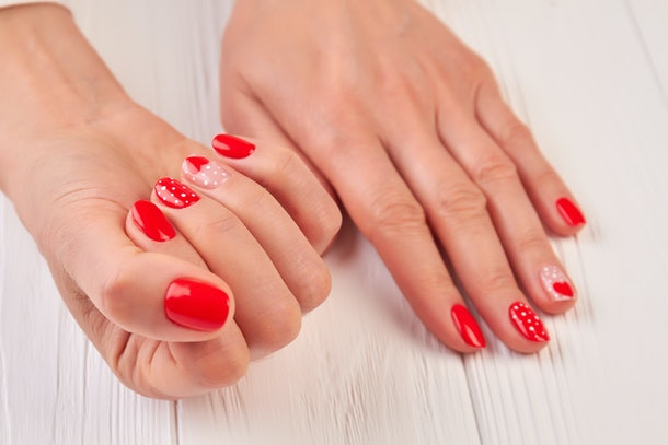 Valentine nail art manicure. Beautiful female manicure on Valentines Day Holiday. Valentines day nail art design.