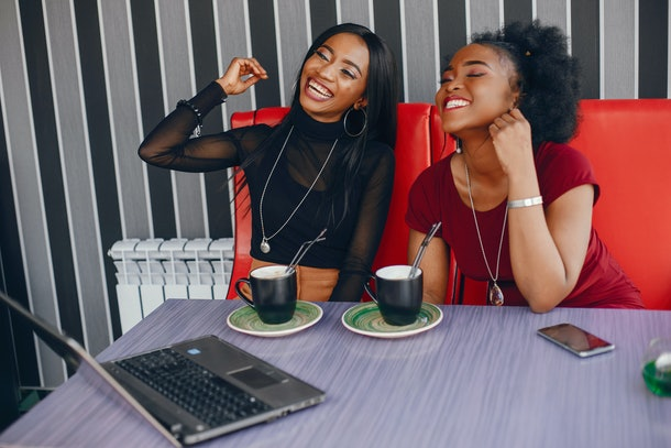 Two trendy woman sit at a table and laugh while enjoying coffee.