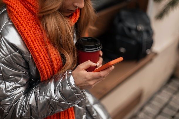 A stylish woman with a metallic puffer coat and bright red scarf holds her to-go coffee cup and phone on a bench.
