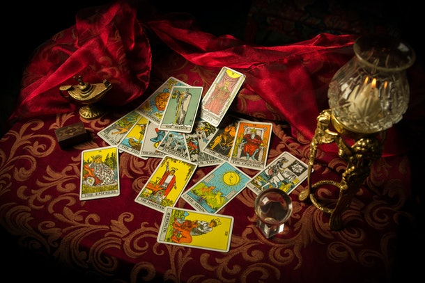 A pile of tarot cards lie scattered and spread across a table top surrounded by multiple occult items.