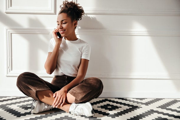 A woman in a T-shirt and capris sits on a tiled floor while smiling and talking on her phone.