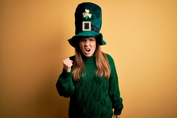 Young beautiful brunette woman wearing green hat on st patricks day celebration angry and mad raising fist frustrated and furious while shouting with anger. Rage and aggressive concept.