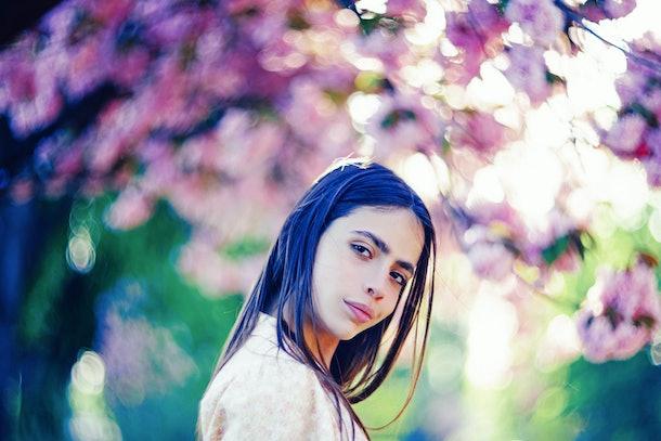 Spring girl face. Close up portrait of tender woman at sakura flowers background. Hanami celebration in sakura blooming garden. Young stylish woman walking in sakura park and enjoy beauty of pink