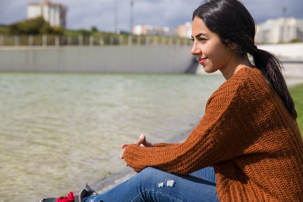 Dreamy pretty woman sitting by city river. Young lady looking away and sitting with distant buildings in background. Spring and leisure concept. Side view.