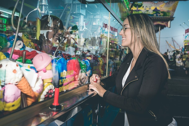 A young woman plays on a claw machine.