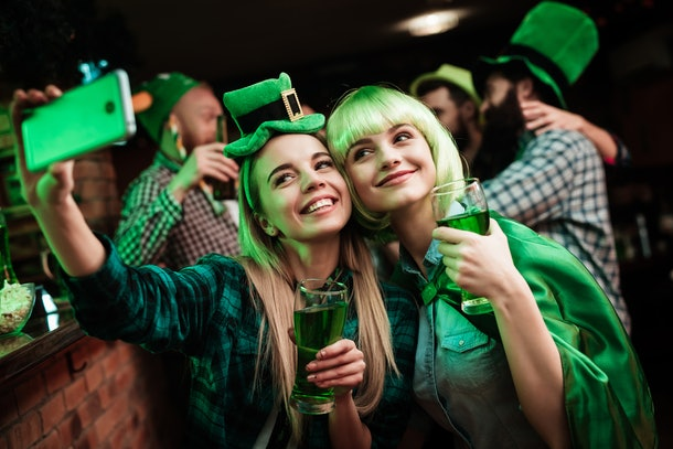 Two girls dressed up for St. Patrick's Day at a bar smile with their green beers for a selfie.