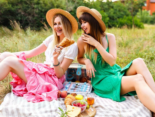 Outdoor countryside portrait of two happy sisters and best friends, enjoying picnic at vintage French style, color matching feminine outfits, tasty food and vine, nice time together.