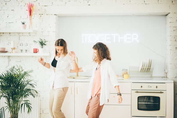 Two women dance in a bright kitchen.