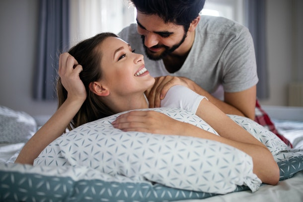 A smiling couple gives each other massages at home.