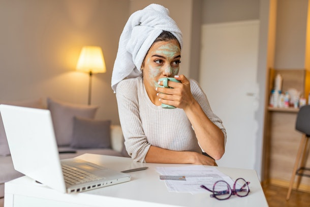 A woman with a towel around her hair and face mask on works from home with her laptop and coffee.