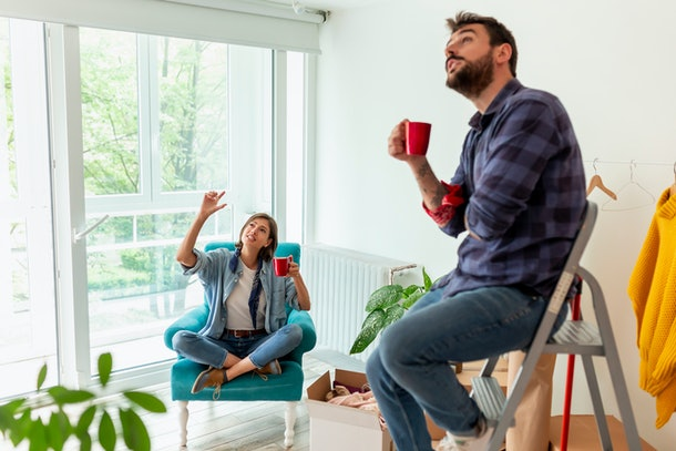 Couple moving in together, taking a break from unpacking the boxes, drinking coffee and planning arrangement and decoration of the place