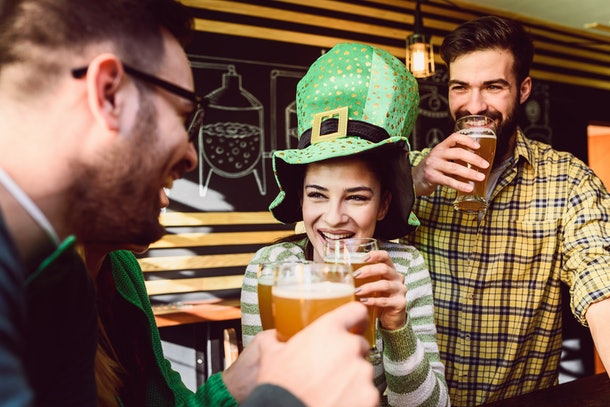 Three friends clink their beers and celebrate St. Patrick's Day at a bar.