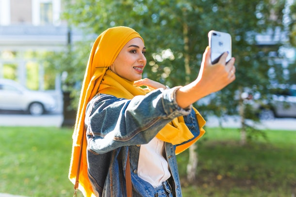 Muslim girl in hijab makes a selfie on the smartphone standing on the street of the city