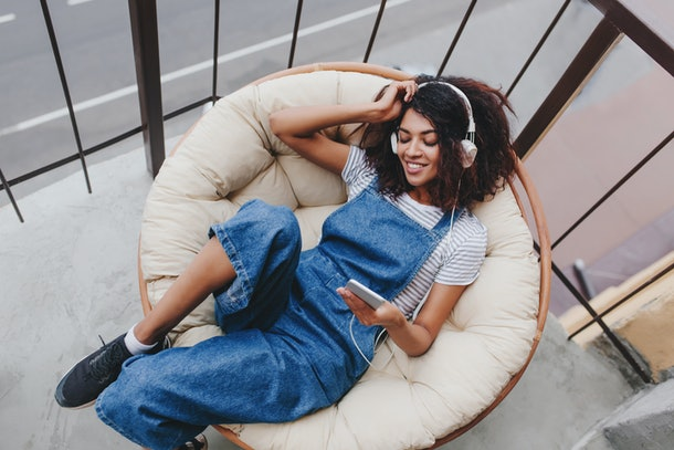 A woman wearing headphones smiles and relaxes on a chair while holding her phone.