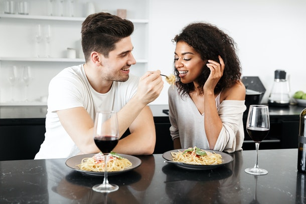 Beautiful young multiethnic couple having a romantic dinner at home, drinking red wine and eating pasta
