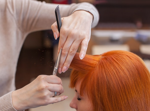 The hairdresser does a haircut with scissors of hair to a young with red hair girl in a beauty salon.