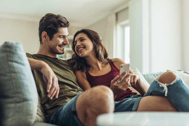 A couple sitting on the couch, smile at each other while looking at a cell phone.